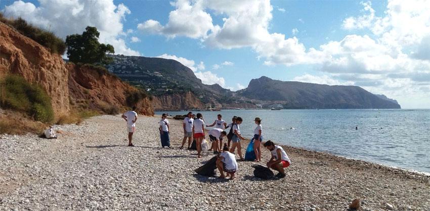 Voluntaris de l'ONG De Amicitia col•laboren en la neteja de la platja després del Castell de l'Olla junt a l'empresa Greenwichdiving